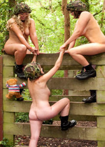 4 naked ladies in combat books climbing over an obstacle wall