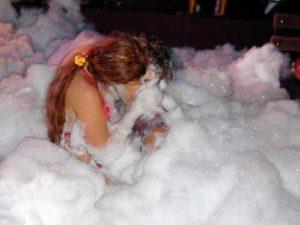 2 ladies kissing covered in foam in a foam pit