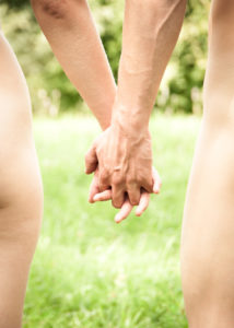 View of a naked couple holding hands outdoors.