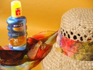 An image of vacation necessities: hat, sunglasses, sun screen