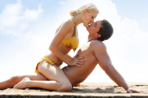 Young beautiful couple kissing on the beach